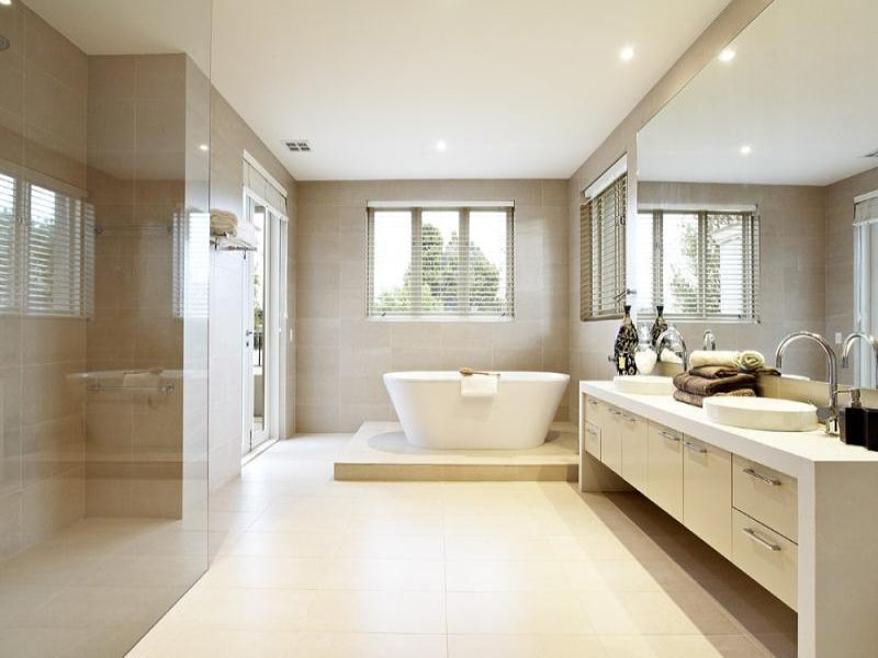 modern bathroom design with bi fold windows using frameless glass