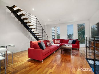 Open plan living room using red colours with hardwood & staircase - Living Area photo 8207177