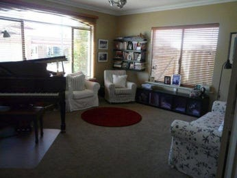 Open plan living room using green colours with carpet & louvre windows - Living Area photo 408921