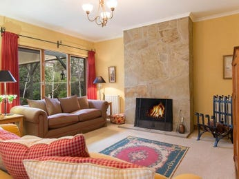 Open plan living room using red colours with stone & fireplace - Living Area photo 8594545