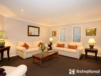Open plan living room using brown colours with floorboards & louvre windows - Living Area photo 210366