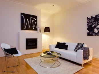 Open plan living room using black colours with floorboards & fireplace - Living Area photo 7429585