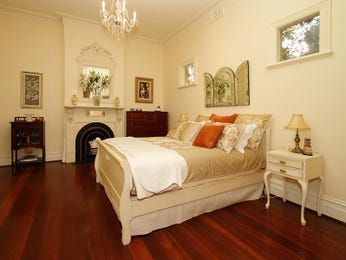 Classic bedroom design idea with hardwood & fireplace using cream colours - Bedroom photo 1311117