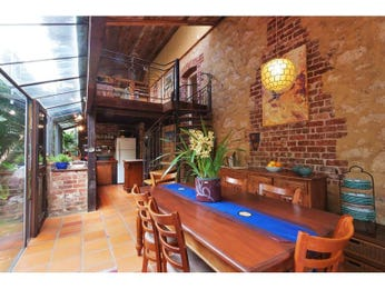 Retro dining room idea with exposed brick & staircase - Dining Room Photo 1589179