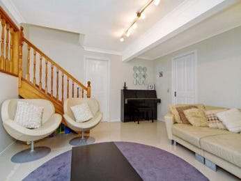 Open plan living room using cream colours with hardwood & staircase - Living Area photo 1520623