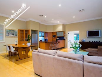 Open plan living room using brown colours with floorboards & louvre windows - Living Area photo 355180