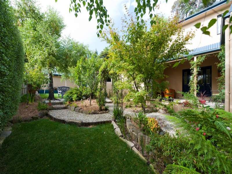 landscaped garden design using grass with retaining wall  u0026 hedging