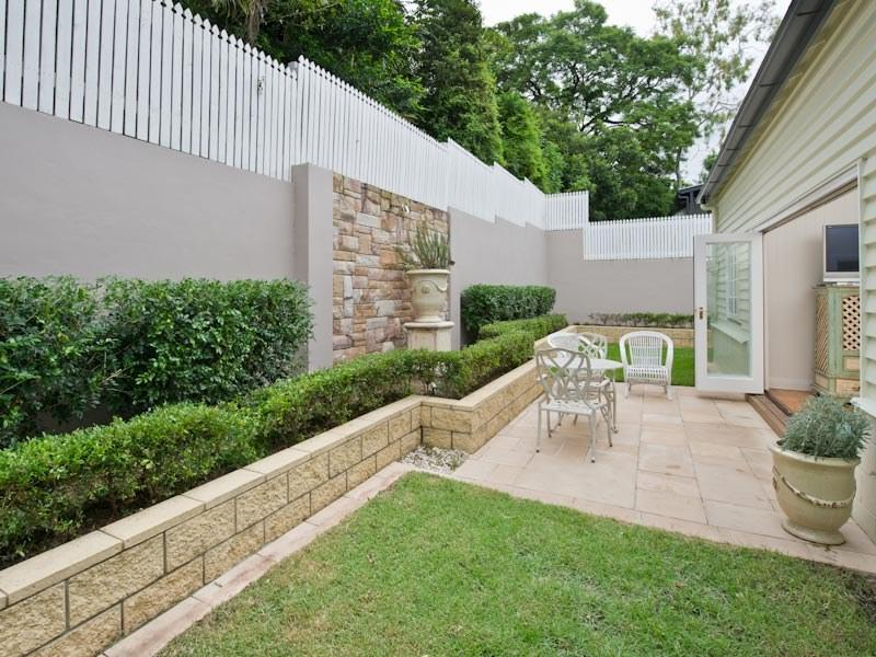 Landscaped garden design using grass with retaining wall