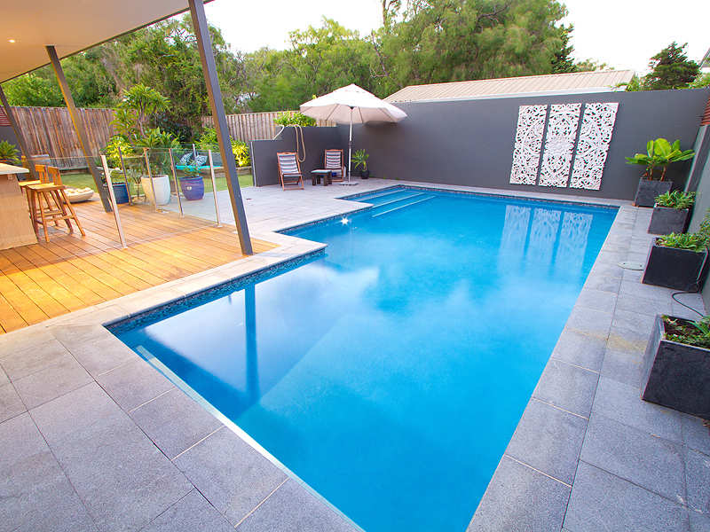Geometric pool design using grass with retaining wall for Pool exterior design