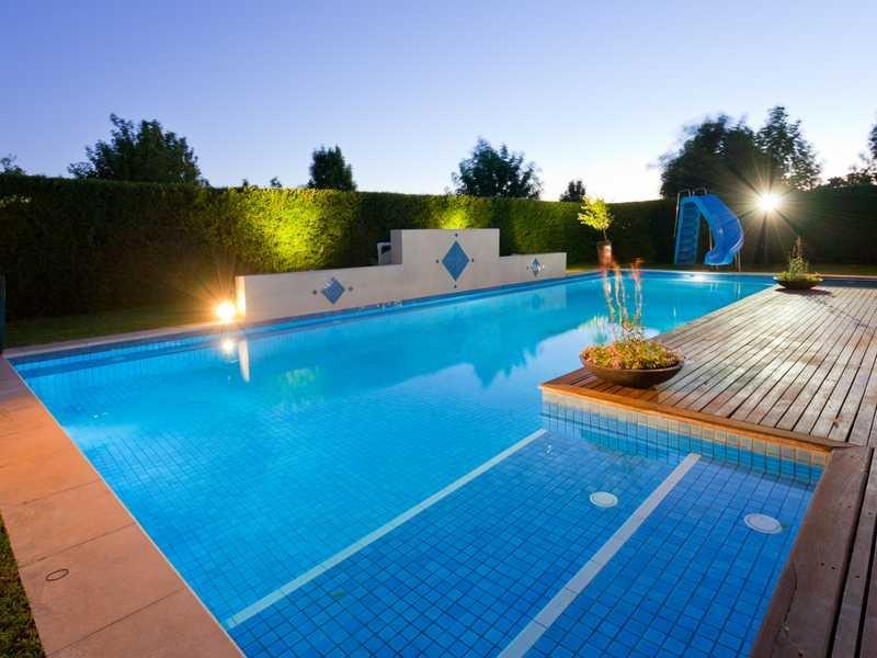 Freeform pool design using bluestone with decking for Pool lighting design